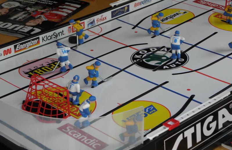 Pöytäjääkiekkopeli, jossa pelaajahahmoilla on päällään Suomen ja Ruotsin peliasut.