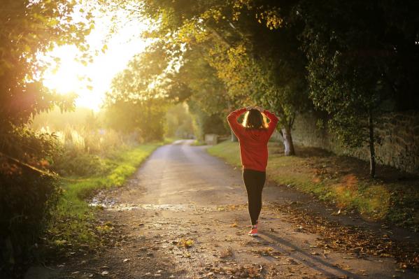 Nainen kävelee metsätiellä ja aurinko paistaa puiden välistä.