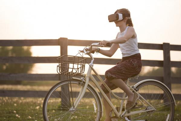 Nainen pyöräilee virtuaalilasit päässään.