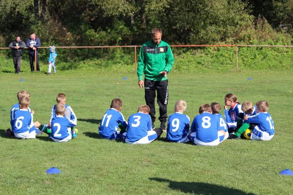 Juniorijalkapallojoukkue kuuntelee valmentajansa ohjeistusta.