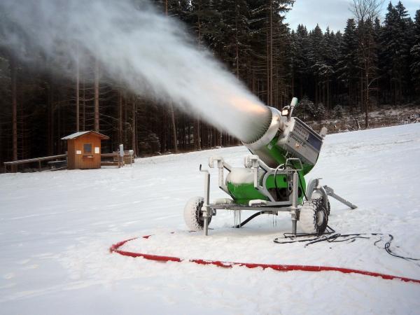 Lumetuskone tykittää lunta laskettelurinteeseen.