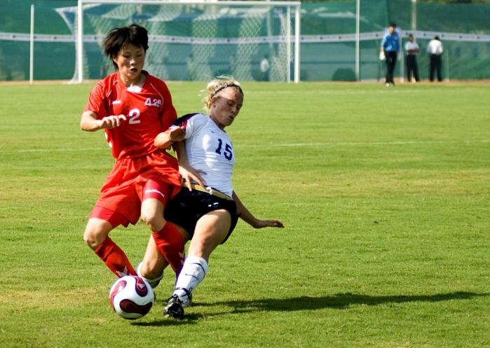 Kaksi naisjalkapalloilijaa taistelee pallosta kentällä.