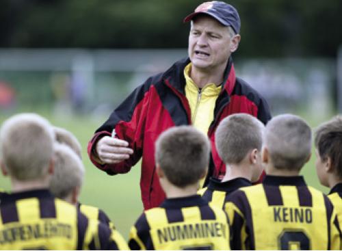 Valmentaja ohjeistaa nuoria pelaajia.