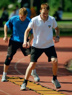 Nuoria urheilijoita treenamassa juoksutikapuilla.