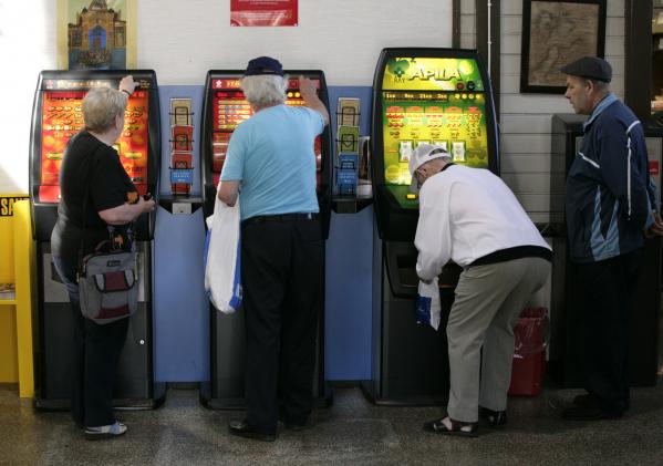 Iäkkäitä henkilöitä pelaamassa rahapeliautomaateilla.