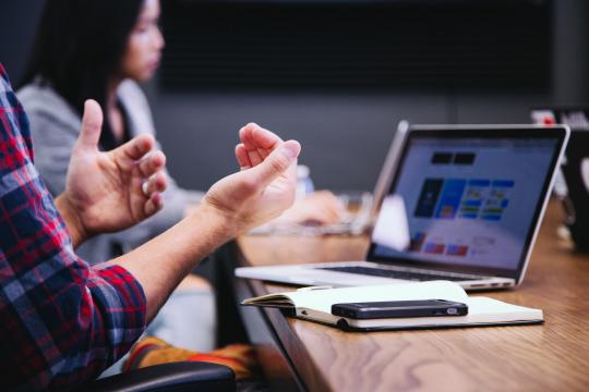 Kaksi henkilöä istuvat pöydän ääressä. Pöydällä on kannettava tietokone, vihko ja älypuhelin. Etualalla oleva henkilö puhuu.