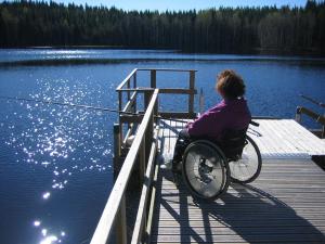 Nainen pyörätuolissa kalastamassa laiturilla